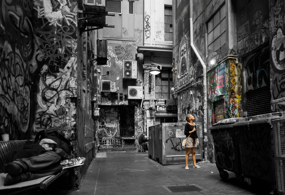 Woman admiring street art, whilst a homeless man sleeps nearby, Laneway, Melbourne 2018