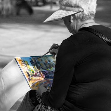 An anonymous old woman paints what she sees while sitting down in a little square in Las Palmas (Canary Islands)