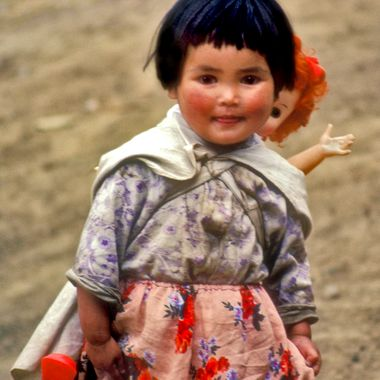 "In 1985, while in Yunnan Province, China we visited the village of Shigu.  It is where the Yangtze River makes a very sharp turn to the North. As I was wandering about taking photos, this little girl appeared behind me. I turned and captured this image, just about the best ""grab shot"" I've ever taken. Since China was still officially closed to Western tourists I have no idea where she got her red-headed Caucasion doll.  Details: Olympus OM-4T, probably a 50 mm lens, either Ektachrome or Velvia film."