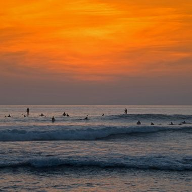 Some surfers wait for the right wave at the sunset.