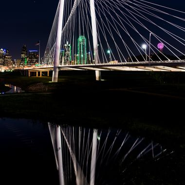 Margaret Hunt Hill bridge in Dallas, Texas. The reflection is in the wetlands of the Trinity River. The Dallas skyline is in the background.