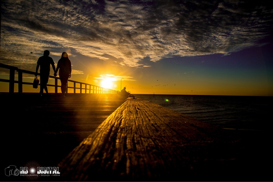 Couple walking along Seaford Pier at Sunset.