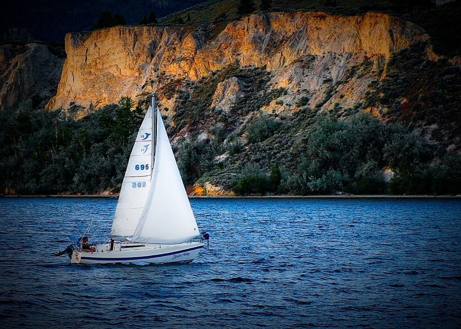 Sailboat sails off the coast of a lake at sunset