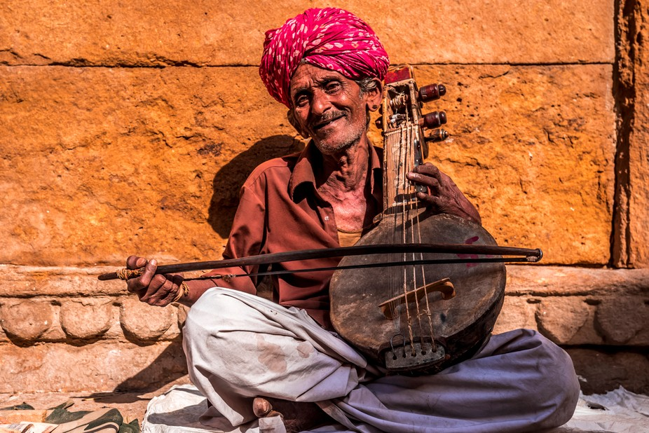 This picture of a smiling old man with his traditional music instrument gives a glimpse of the in...