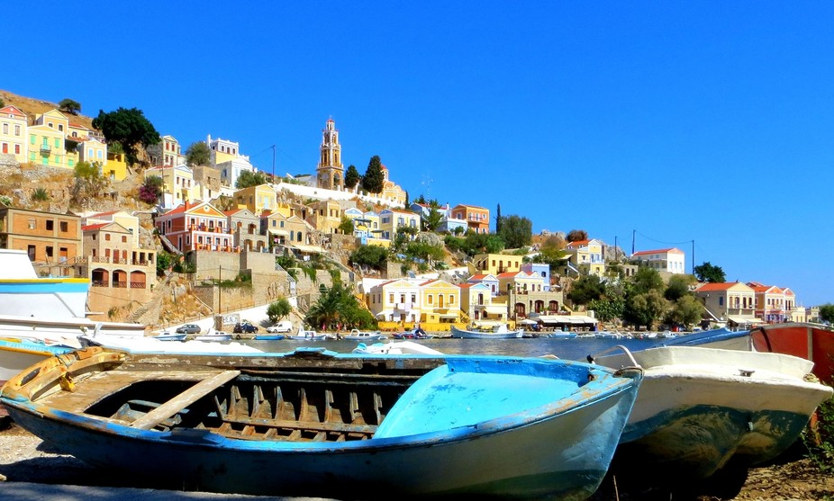 Old boats on the quayside in Symi harbour Greece