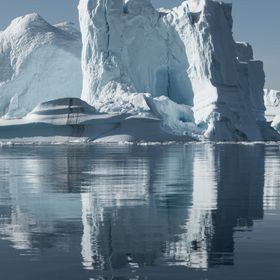 ice berg reflecting in ice cold blue waters