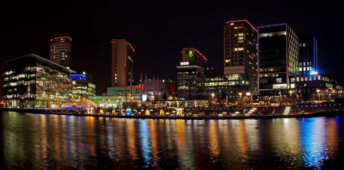 Looking across the water at night towards Media City, Salford Quays, Manchester.