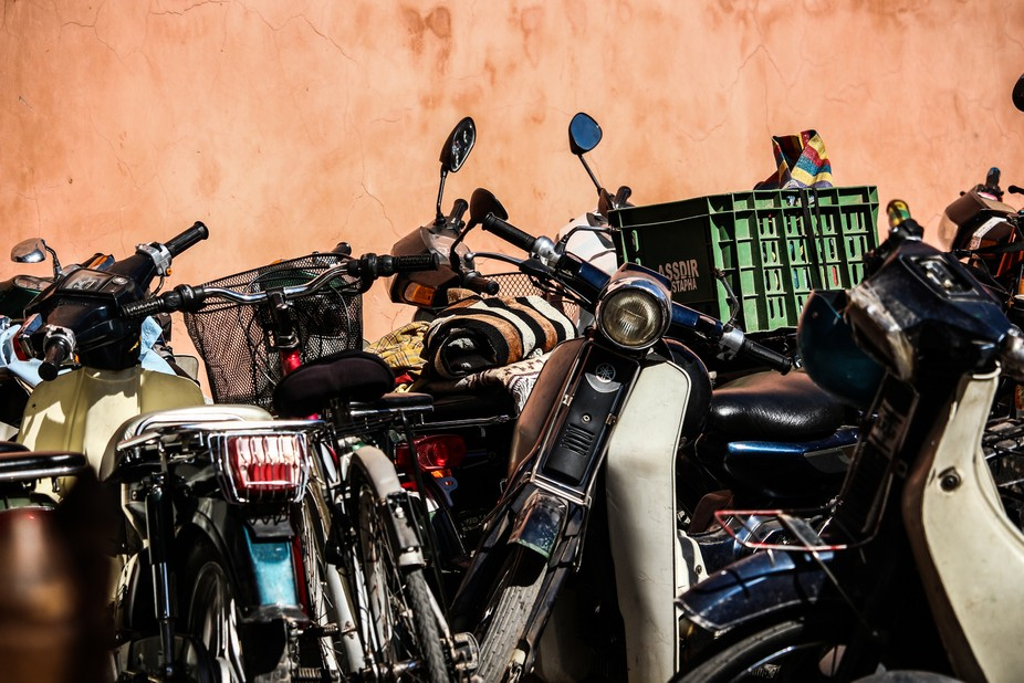 Mopeds are parked up against each other, against a wall, in the Medina of Marrakech, Morocco.