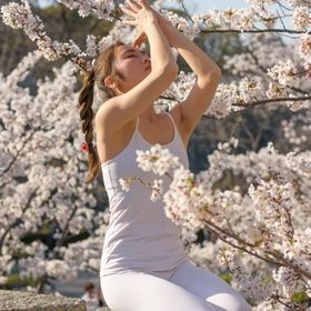 A girl practicing yoga, while surrounded by cherry blossom flowers, with main tower of Osaka castle in the background, Osaka, Japan.