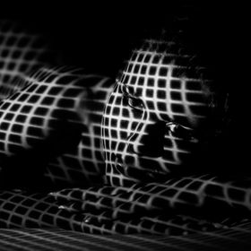 A young woman laying in a pattern of light.