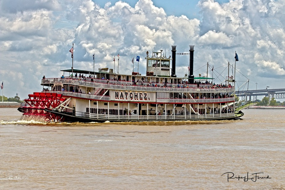 The Riverboat Natchez heading up the Mississippi river in New Orleans