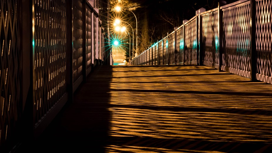 Brilliant star shaped bokeh in background with shadow on the sidewalk of the bridge deck.