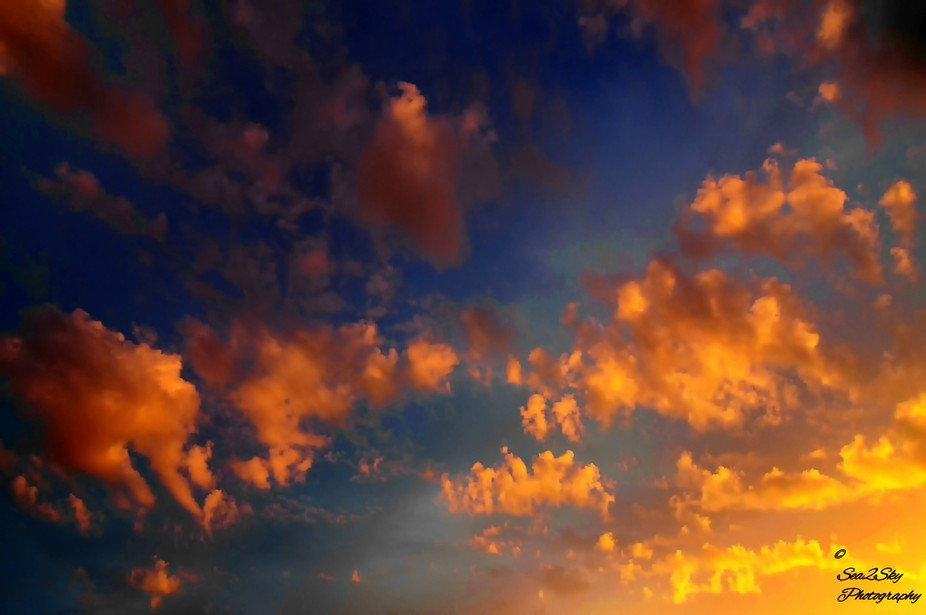 Unusually low clouds set against a sea of higher clouds and sky with the sun setting on Whidbey I...