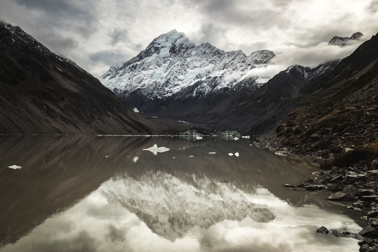 At the end of hooker valley track in the mount cook national park the tallest peak in New Zealand is reflecting in a calm lake formed by the glacier water at his feet.