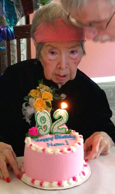 Great Grandma needs a little help blowing out Happy Birthday candles!