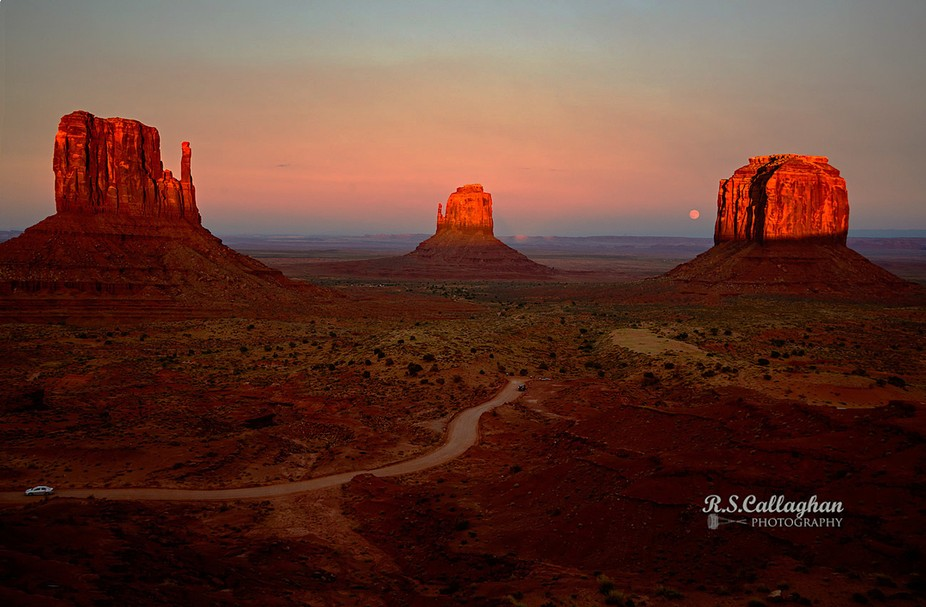 The full moon is rising as the last rays of the sun hit the buttes at Monument Valley. I included the car in the bottom left to show how enormous these buttes are.