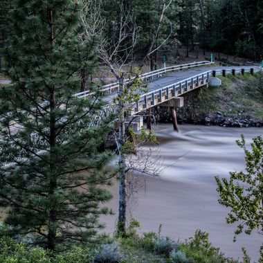 The Nicola River at flood levels is racing by the Petit Creek Bridge