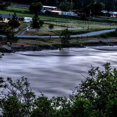 The Nicola River at flood levels goes screaming by Petit Creek Bridge near Merritt B C