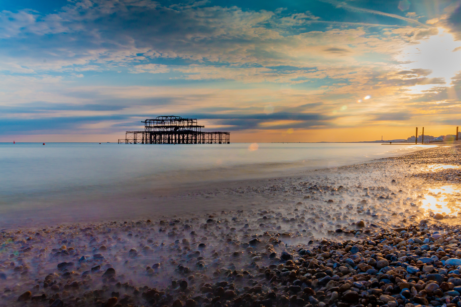 A slow exposure of West Pier at sunset with the pebble beach in the foreground.