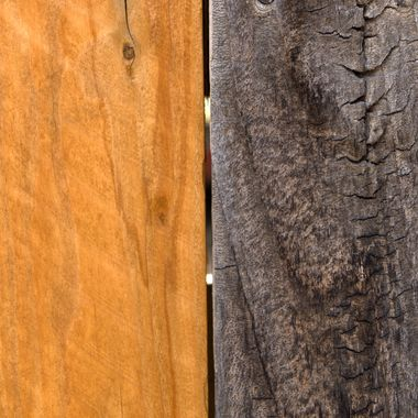 A new fence board beside a weathered fence board