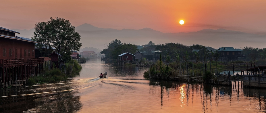 A small river boat heads of to the main lake of Inle Lake Burma as the sunrises over the mountains