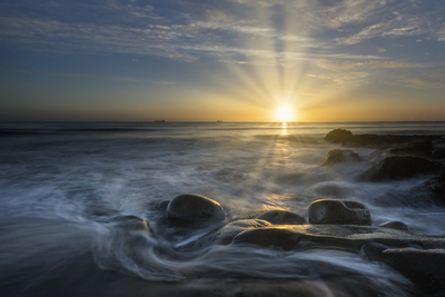 Sun kissing wet stones at sunset
