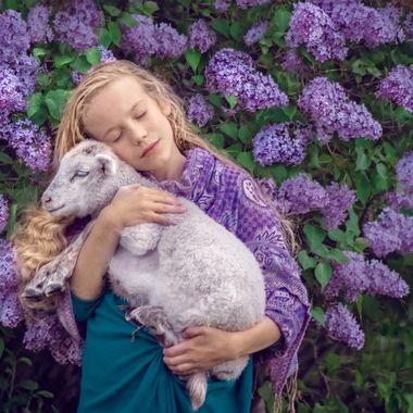 Little girl loving a spring lamb.
