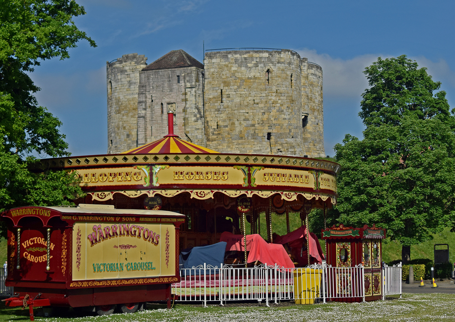 Carousel and Castle at York.Clifford tower behind Victorian carousel outside York museum.
