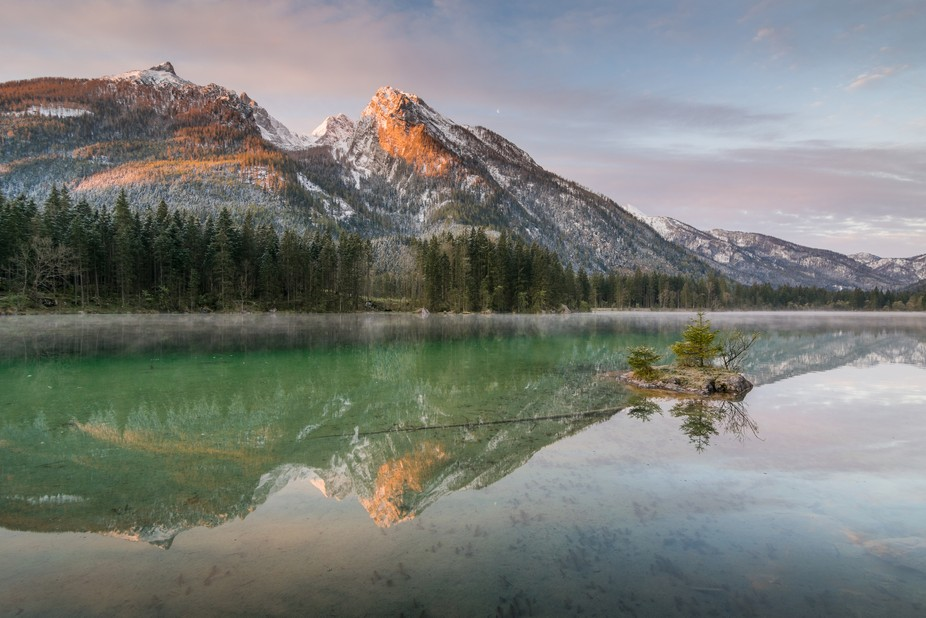 The first light touching mountain Hochkalter which is reflected on lake Hintersee