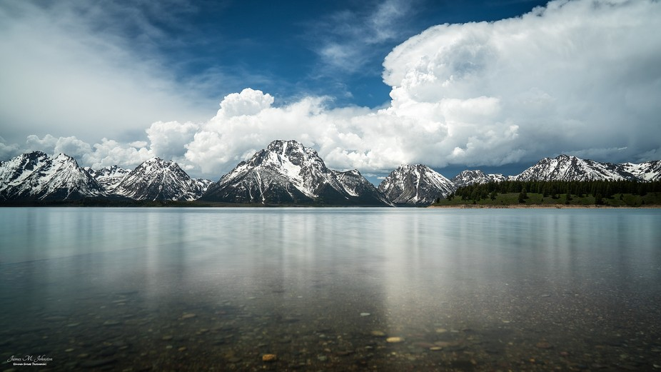 Afternoon storm clouds build over the Tetons and reflect on Jackson Lake in this mid afternoon im...