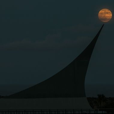 The moon rising over a statue.