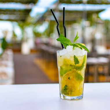 a chilled lime green mojito cocktail on a rooftop bar