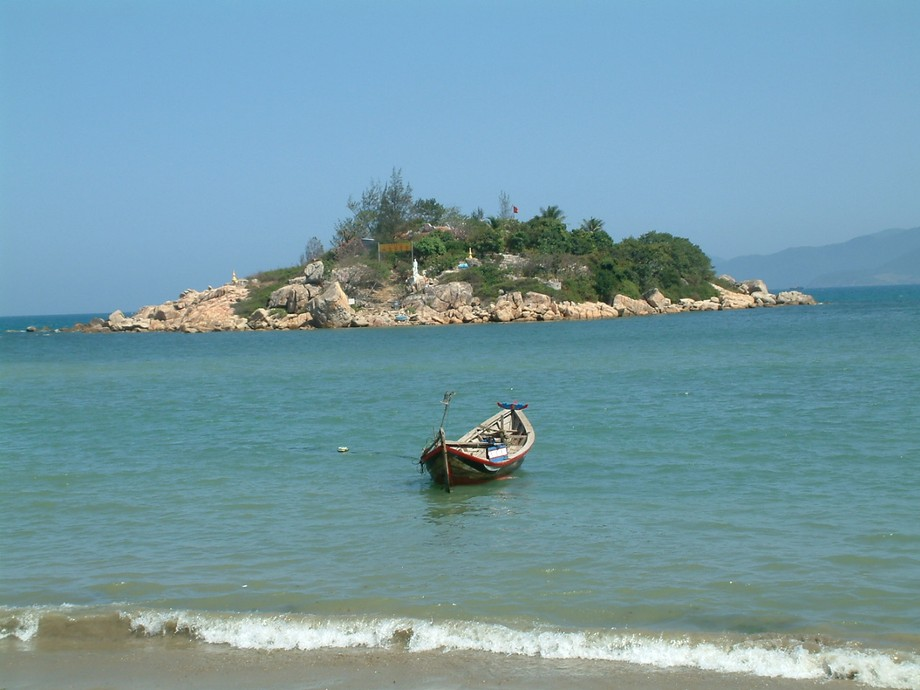 Small boat off the beach at Nha Trang Vietnam. Buddhist retreat in the backbround