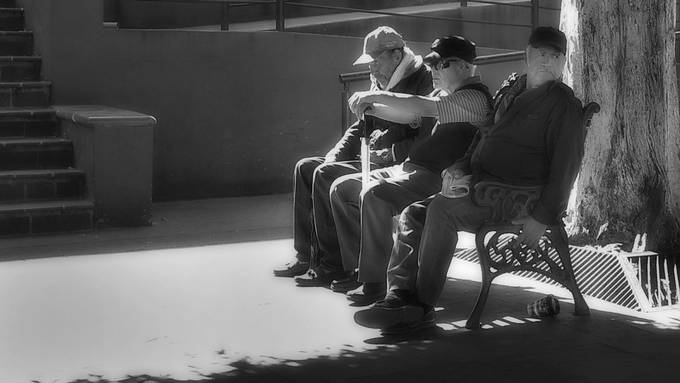 Guanajuato Mexico. Three gentleman, resting on the bench beside the town market