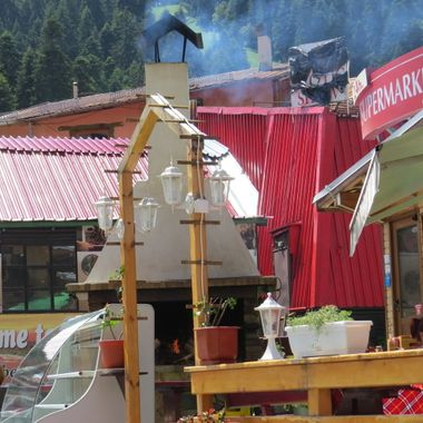 This image was taken in Borovets, Bulgaria. You can see smoke rising from the top of a large, round, stove oven used in food preparation.