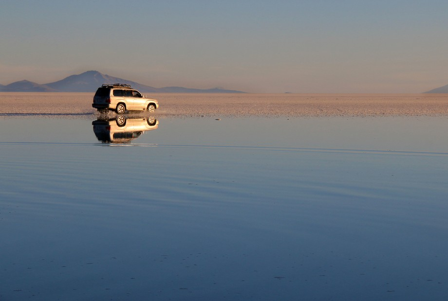A Land Cruiser sets off across the salt as the sun starts to set. The lake is formed at the edge of the salt flats from rain draining from the mountains. The salar is at 12'000 feet.