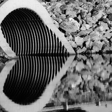 The reflection of a culvert near the river.