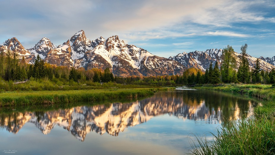 Further up the Snake River from Schwabacher's Landing, the morning sunrise gives a warm ...