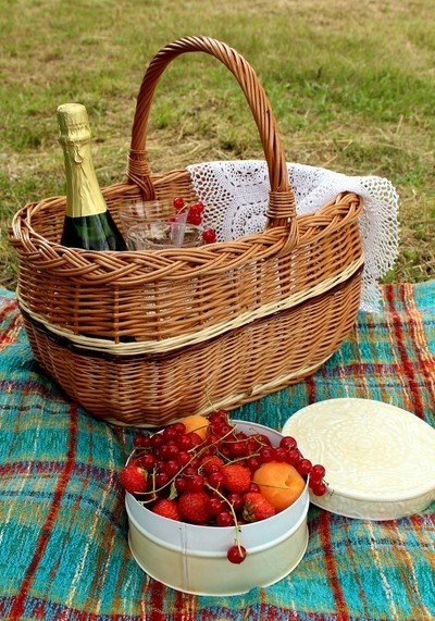 Summer activities - picnic basket with a bottle of champagne and white box full of fresh organic fruit from the garden