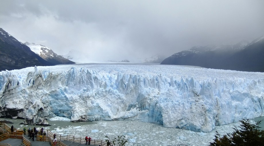 Standing in front of a glacier and watching it calve into the water, hearing the sounds of ice br...