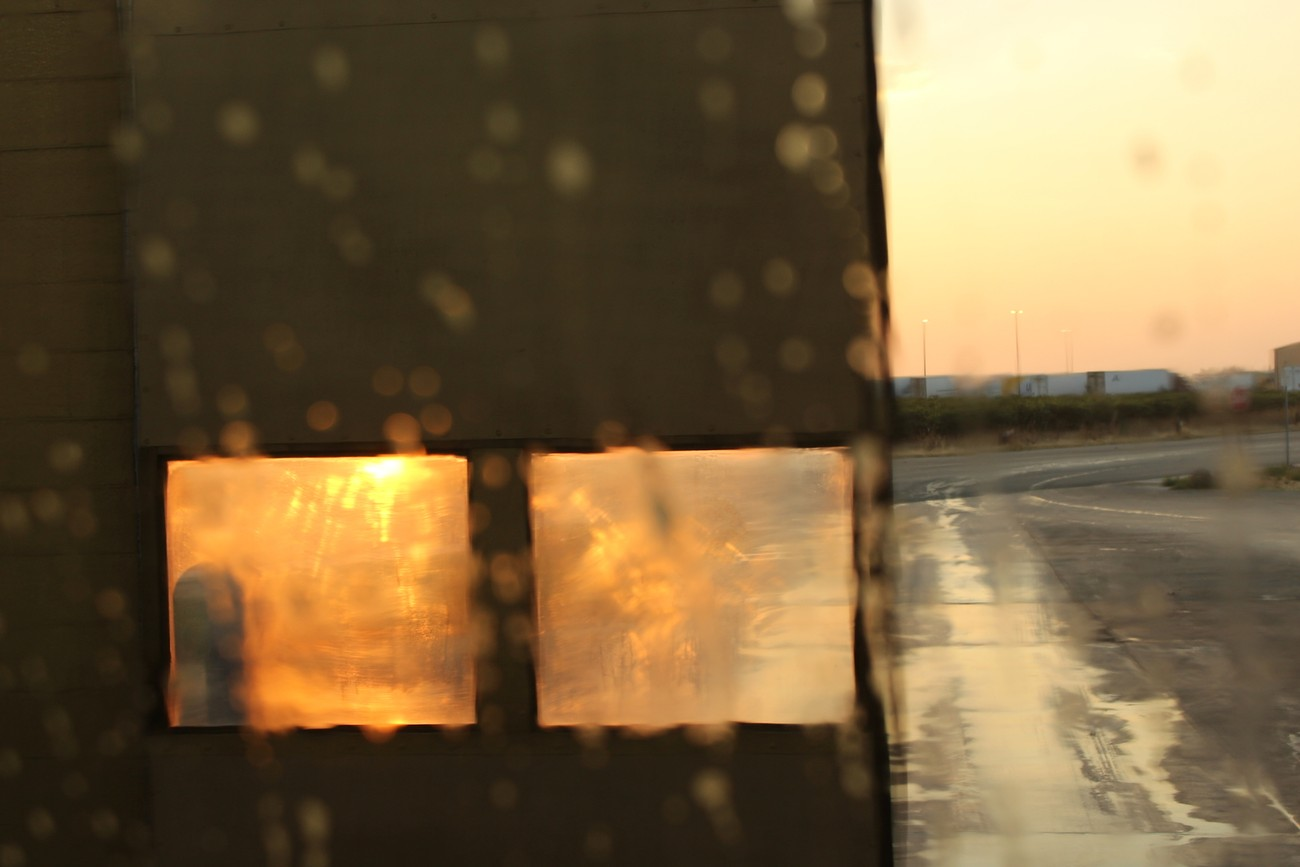August 18, 2017. Inside a Truck Wash during a truck wash. The sun was coming up through the bay door windows and door was half open