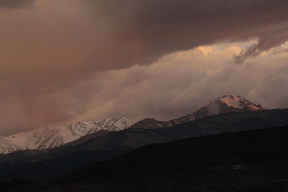 Storm clouds passing over the snow capped mountains at sunset. soft light and the setting sun created a hazy, almost dirty, colours that blend into the cloud and reflections on the snow.