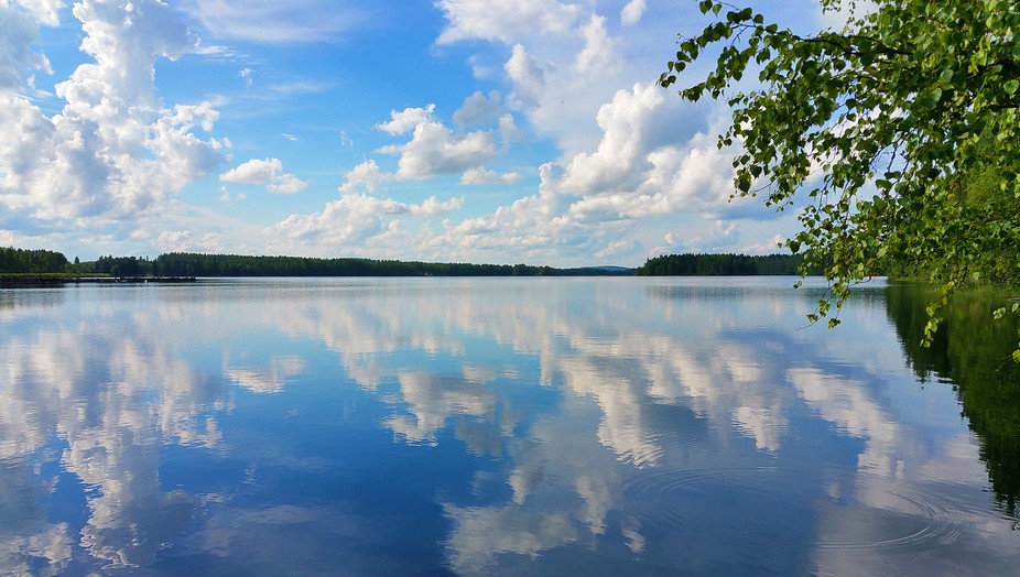 Reflection of clouds on calm surface of lake