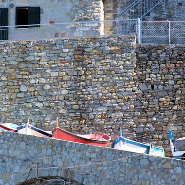 These small boats are a colorful contrast to the pattern in the stone wall.