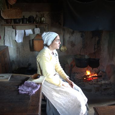 This is a re-enactor at Plimoth Village, MA.  Everything is realistic, from her clothing to the chicken cooking in the pot.