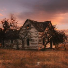 An abandoned house in the country with a beautiful sunset in play creates a majestic wonderful seen!