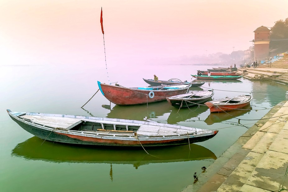 Wooden boats at sunrise on the Ganges river in Varanasi India.