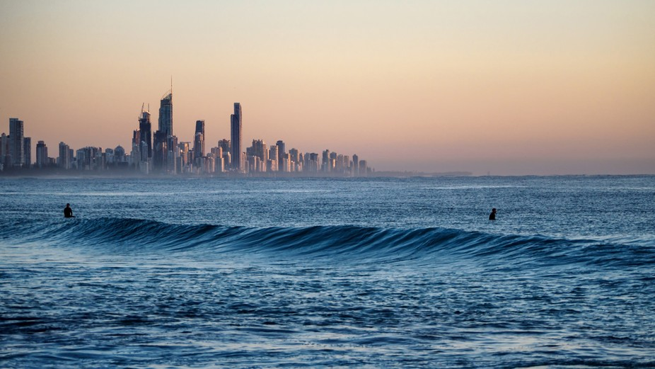 Sunrise over Surfers Paradise, with surfers waiting for the perfect wave, The city appears to be ...
