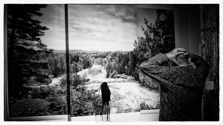 L'artiste Réal Capuano regardant son oeuvre contre les piplines, photo prise sur le vif.