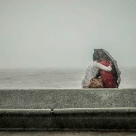 A young couple share a tender moment, mindless of the pouring rain.